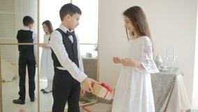 Den tonåriga pojken ger en flicka en gåva för en ferie, lager videofilmer