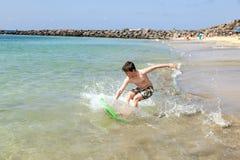 Den tonåriga pojken har gyckel med hans boogiebräde Fotografering för Bildbyråer