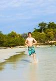 Den tonåriga pojken kör längs den tropiska stranden Arkivbilder