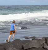 Den tonåriga pojken kör längs en svart vulkanisk strand fotografering för bildbyråer