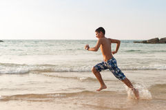 Den tonåriga pojken kör längs stranden Arkivbild
