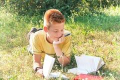 Den tonåriga pojken ligger på gräset och läseböckerna royaltyfria foton