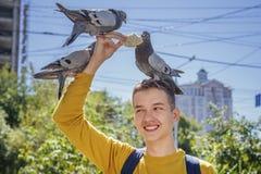 Den tonåriga pojken matar duvor på stadsgatan arkivbild