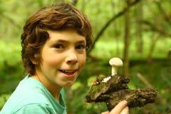 Den tonåriga pojken med regn plocka svamp i skogen royaltyfri bild