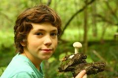 Den tonåriga pojken med regn plocka svamp i skogen royaltyfri fotografi