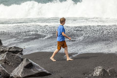 Den tonåriga pojken promenerar en svart vulkanisk strand Royaltyfri Fotografi
