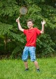 Den tonåriga pojken som spelar badminton parkerar in Fotografering för Bildbyråer