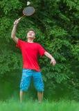 Den tonåriga pojken som spelar badminton parkerar in Royaltyfri Foto