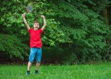 Den tonåriga pojken som spelar badminton parkerar in Royaltyfri Fotografi
