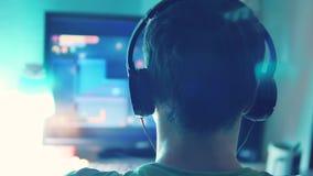 Den tonåriga pojken spelar online spelet på datoren via internetbildskärm i hörlurar tonåringmannen spelar en video livsstillek p lager videofilmer