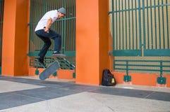 Den tonåriga skateboradåkaren hoppar flip Fotografering för Bildbyråer
