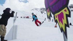 Den tonåriga snowboarderen gör flip från språngbrädan Kosmiska objekt för papp cameraman stock video