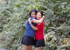Den tonårs- Amerasian flickan i tillgiven kram med hennes koreanska moder, Snoqualmie parkerar, staten av Washington royaltyfri bild