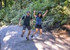 Den tonårs- Amerasian flickan och hennes Caucasian fadern som dansar upp en brant kulle, Snoqualmie parkerar, staten av Washingto fotografering för bildbyråer