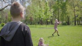 Den tonårs- blonda pojken som spelar frisbeen i, parkerar med hans moder Barnet som kastar leksaken utan kvinnan, fångar inte den stock video