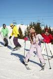 Den tonårs- familjen skidar på ferie i berg Fotografering för Bildbyråer