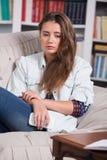 Den tonårs- flickan är skriande sammanträde på soffan Arkivfoton