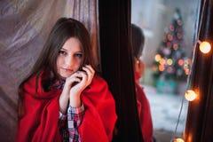 Den tonårs- flickan dolde en röd filt Royaltyfri Fotografi