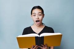 Den tonårs- flickan har chockat uttryck, medan läsa ett lärobokutbildningsbegrepp royaltyfri foto