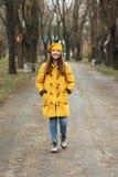 Den tonårs- flickan i ett gult lag som går i, parkerar arkivfoto