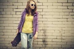 Den tonårs- flickan i jeans och solglasögon rymmer skateboarden Royaltyfria Bilder