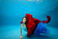 Den tonårs- flickan i klänningen simmar undervattens- längst ner av pölen, spelar med ett rött, och den blåa torkduken, ser kamer Royaltyfria Bilder