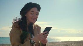 Den tonårs- flickan läser nyheterna i socialt netto i mobilt och ler i strand stock video