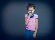 Den tonårs- flickan lider en näsduk på grå färger Royaltyfri Fotografi