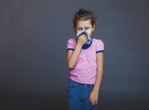 Den tonårs- flickan lider en näsduk på grå färger Arkivbild