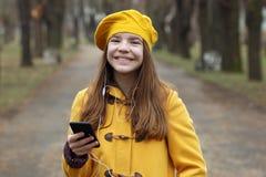 Den tonårs- flickan lyssnar till musik på smartphonen royaltyfria bilder
