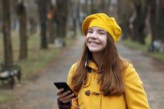Den tonårs- flickan lyssnar till musik på smartphonen arkivfoto
