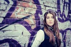 Den tonårs- flickan med hörlurar near grafittiväggen Royaltyfria Foton