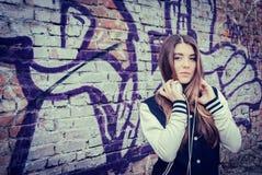 Den tonårs- flickan med hörlurar near grafittiväggen Arkivbild