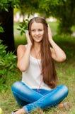 Den tonårs- flickan med hörlurar near trädet Royaltyfria Foton