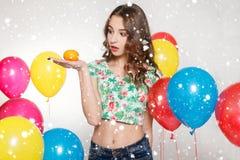 Den tonårs- flickan med helium sväller över grå bakgrund arkivfoton