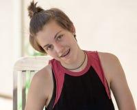 Den tonårs- flickan med sammanträde för kort hår med hennes huvud vippade på till hennes rätt Royaltyfri Fotografi