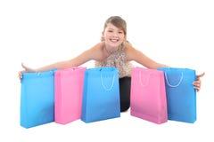 Den tonårs- flickan med shopping hänger lös över vit Fotografering för Bildbyråer