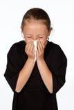 Den tonårs- flickan nyser med ett silkespapper som isoleras på vit Fotografering för Bildbyråer