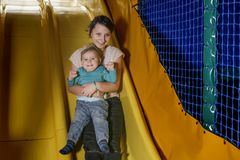 Den tonårs- flickan och ett småbarn är lyckligt rullande down kullen Arkivbild