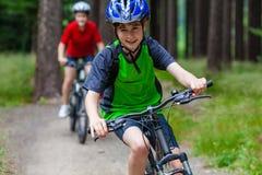Den tonårs- flickan och pojken som cyklar på skog, skuggar Royaltyfria Foton