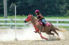 Den tonårs- flickan på hästrygg springer runt om en pol Royaltyfri Fotografi