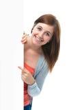 Den tonårs- flickan pekar henne fingret på ett blankt bräde arkivbilder