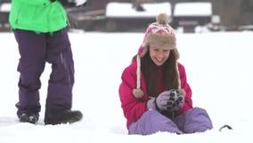Den tonårs- flickan sitter i snö stock video
