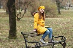 Den tonårs- flickan sitter på bänken royaltyfria bilder