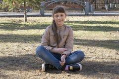 Den tonårs- flickan sitter på jorden i parkera Royaltyfri Fotografi