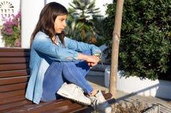 Den tonårs- flickan som sitter på en bänk i, parkerar under vårsolnedgång arkivbilder
