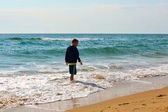 Den tonårs- pojken går på kusten arkivbilder