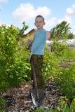 Den tonårs- pojken med en skyffel Royaltyfri Bild