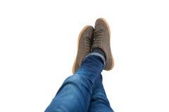 Den tonårs- pojken som ligger med ben, korsade på ankeln på vit bakgrund Arkivbild