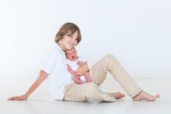 Den tonårs- pojken som spelar med hans nyfött, behandla som ett barn brodern Arkivfoton
